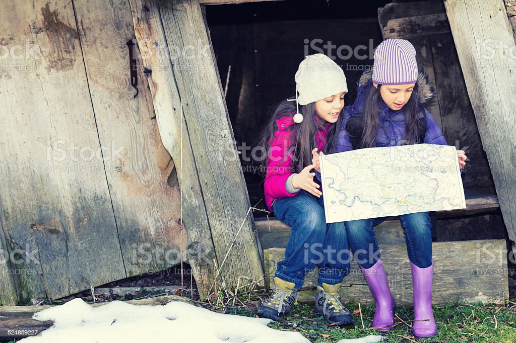 Young girls in countryside looking for directions on the map stock photo