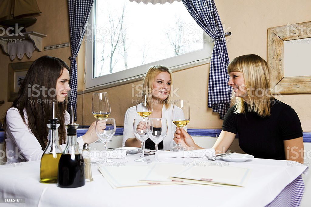 Young girls in fancy restorant making toast with white vine stock photo