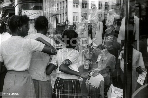 New York City, NYS, USA, 1951. Afro-American teenagers in front of a shop window in Harlem. They look at the offers of a fashion store.