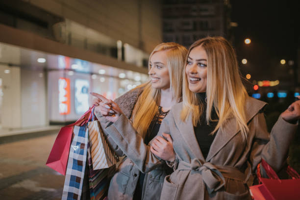young girls in night shopping - dtephoto stock photos and pictures