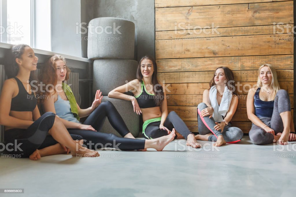 Girls in sportswear having rest after fitness training. Group of...