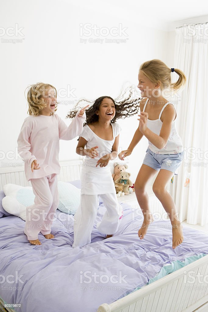 Young Girls Jumping On A Bed stock photo
