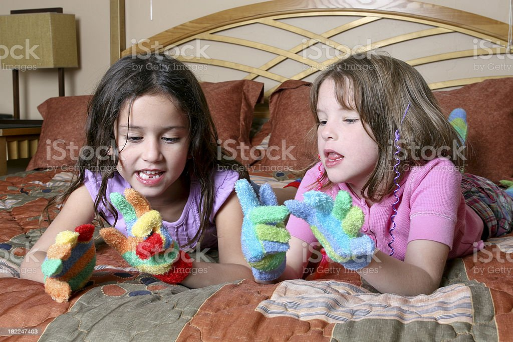 Young Girls Lying on Bed Playing royalty-free stock photo