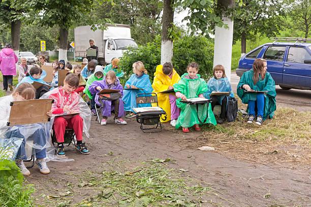 junge mädchen in bunten regenmänteln maler zeichnen von leben - bemalte turnschuhe stock-fotos und bilder