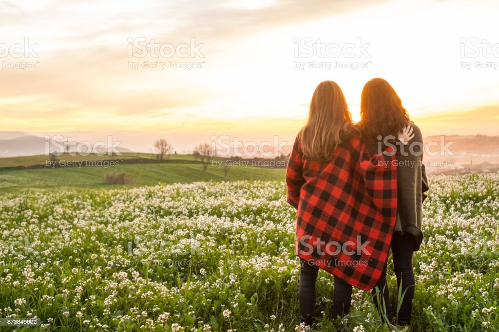 Young girls photographing sunset stock photo