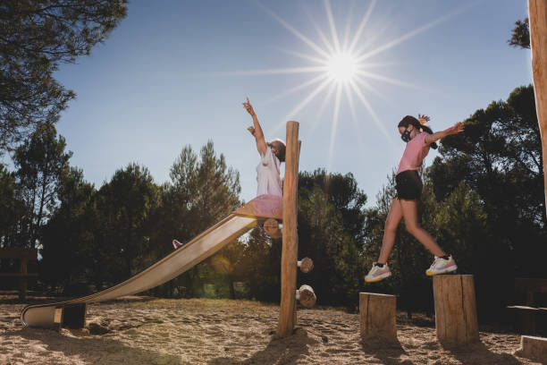 Young girls playing on a wooden playground. stock photo