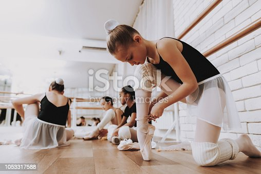 Young Girls Preparing for Ballet Training Indoors. Classical Ballet. Girl in Balerina Tutu. Training Indoor. Cute Dancers. Performance in Hall. Dancing Practice. Girls in White Dresses.