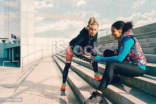 Two friends outside discussing social media before workout