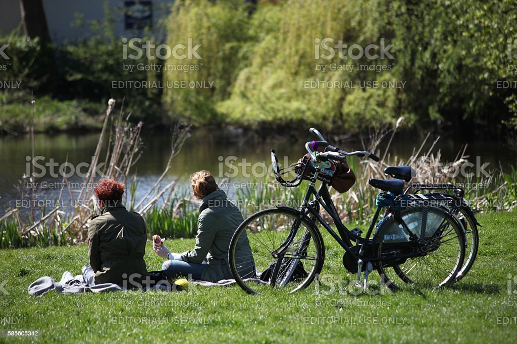 Young girls students are riding bicycle in Amsterdam Vondelpark stock photo