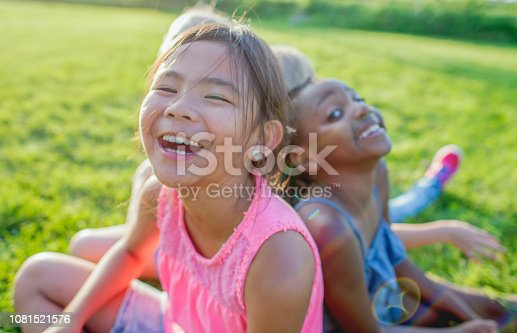 Three elementary school girls sit on the grass in a park, laughing.