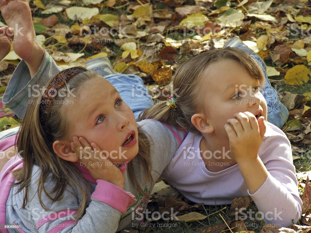 young girls watching leaves fall from the sky royalty-free stock photo