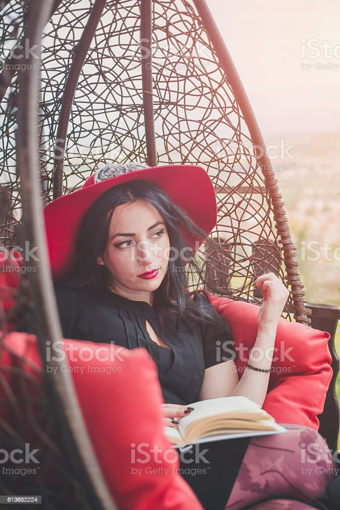 Young glamorous woman relaxing in swing chair , reading book stock photo