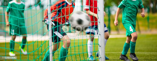 istock Young Goalkeeper Saves. Football Horizontal Background. Junior Soccer Goalkeeper Saving on a Goal 1153933880