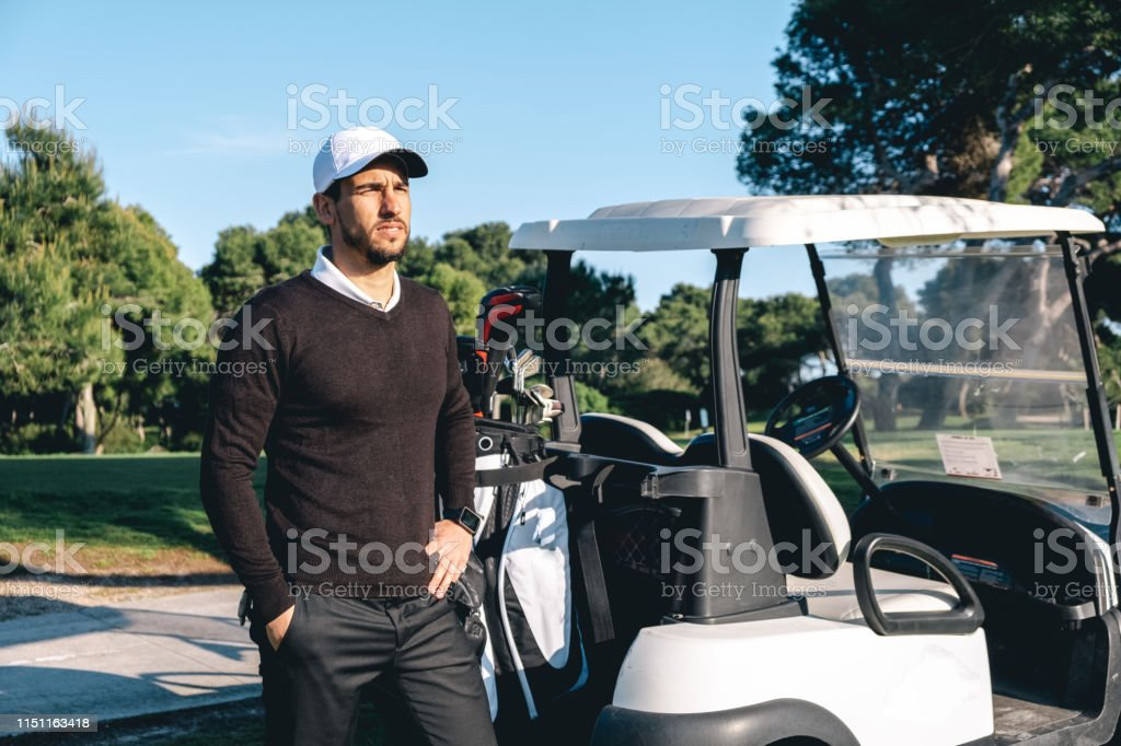 Young golf player poses on a golf course next to a golf cart in a...