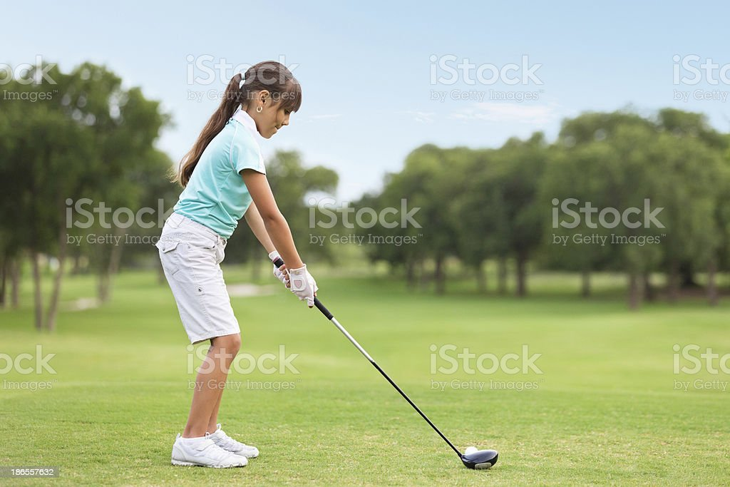 Young golf player teeing off on course stock photo
