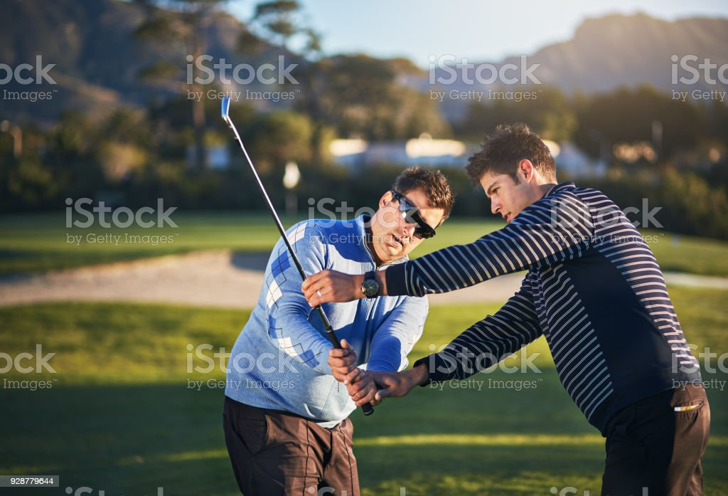 A young golf professional leans forward to correct the stance and...