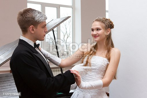 578573556istockphoto Young good looking couple in evening dress and dress coat posing in elegant way in a classical style 1127275346