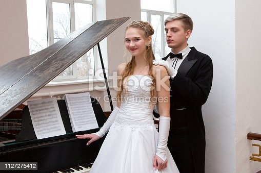 578573556istockphoto Young good looking couple in evening dress and dress coat posing in elegant way in a classical style 1127275412