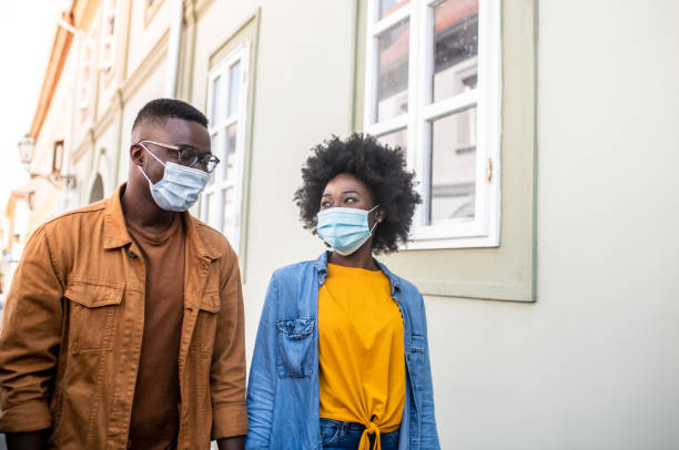 Young gorgeous african hipster couple holding hands and walking down the street during corona virus outbreak. stock photo