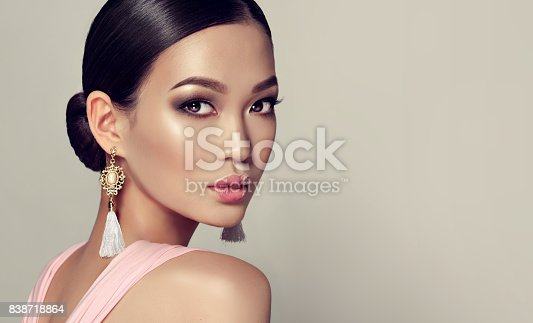 istock Young, gorgeous asian woman in a smoky eyes style make up and tassel earrings 838718864