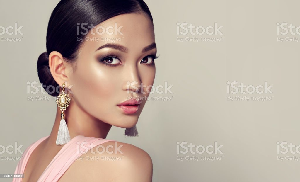 Young, gorgeous asian woman in a smoky eyes style make up and tassel earrings stock photo