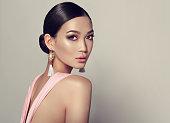 若い、スタイルを作る、煙のような目でゴージャスなアジア女性はタッセル ピアスに身を包んだ。