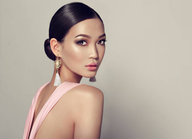 Young, gorgeous asian woman in a smoky eyes style make up, dressed in a tassel earrings. - foto stock