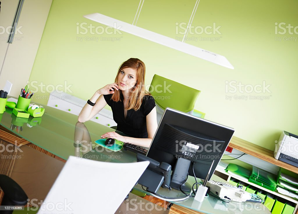 Young gorgeous business woman at desk looking into camera stock photo