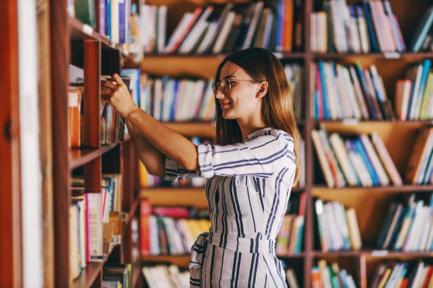 Young gorgeous female student standing next to book shelves and searching for the book for exams. stock photo