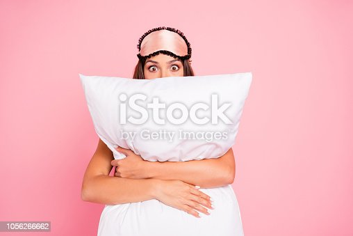 istock Young gorgeous shocked lady wearing eye mask, hugging pillow, hiding. Isolated over pink pastel background 1056266662