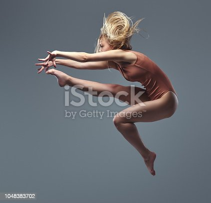 istock Young graceful ballerina dances and jumps in a studio. Isolated on a gray background. 1048383702