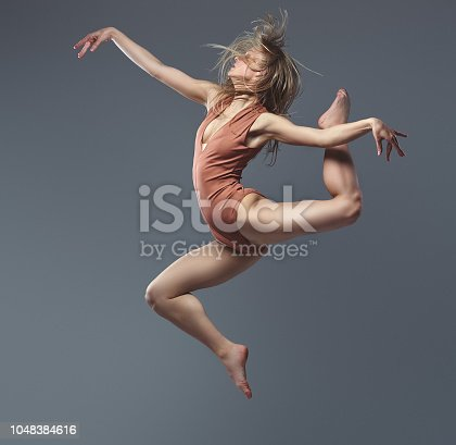 Young blonde graceful ballerina dances and jumps in a studio. Isolated on a gray background.