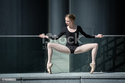 Young graceful ballerina in black bathing suit on a background of the urban industrial landscape. Snapshot on the territory of modern stadium. Kiev.