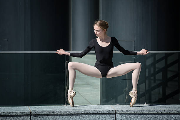 young graceful ballerina in black bathing suit on a background - leotard stock pictures, royalty-free photos & images