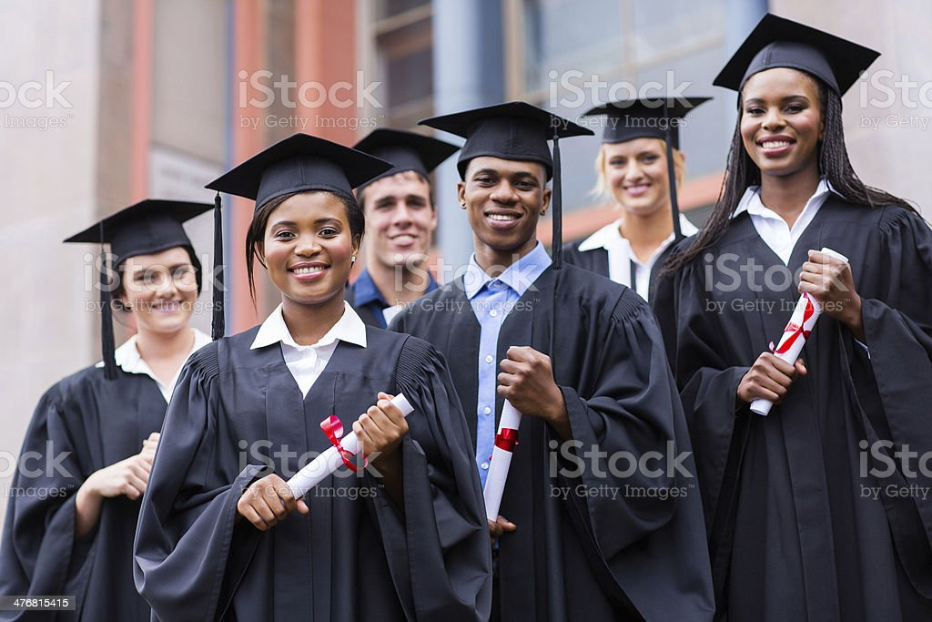young graduates standing in front of university building stock photo