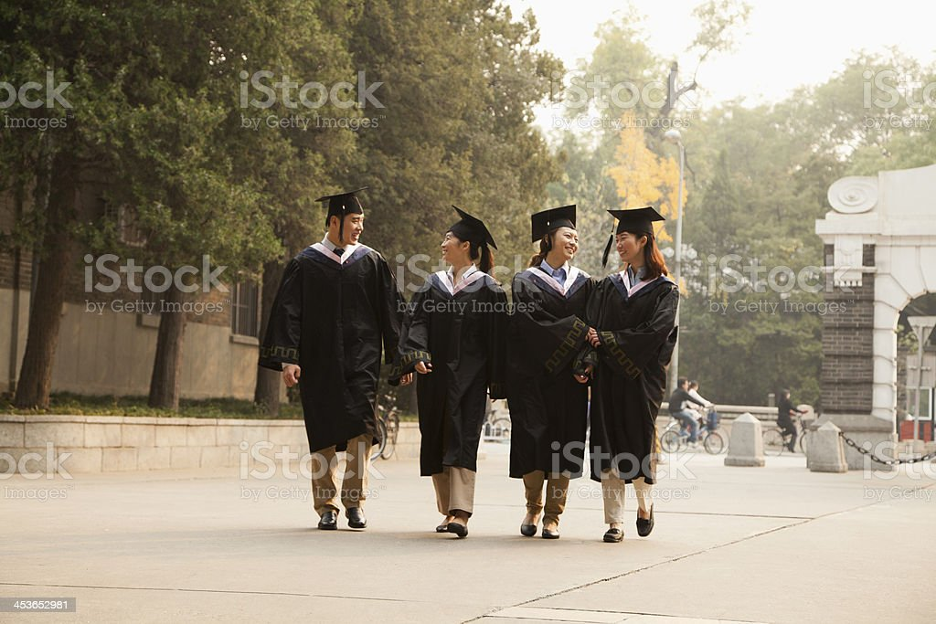 Young Graduates Walking Across Campus stock photo