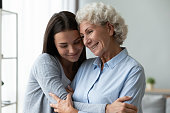 istock Young granddaughter snuggle to elderly grandmother family enjoy time together 1247568870