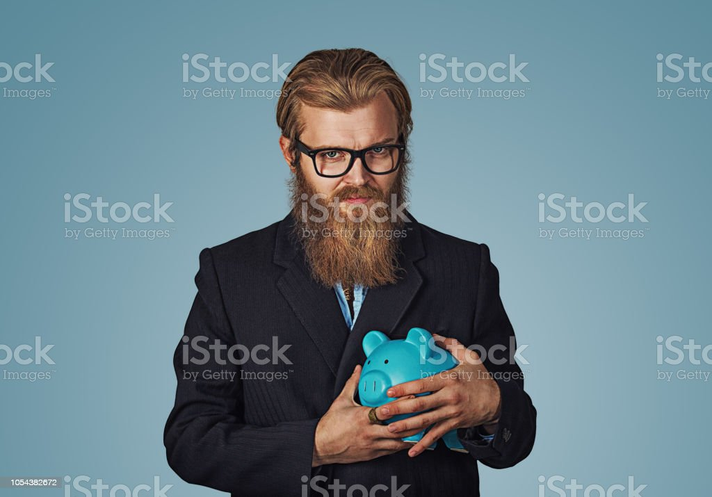 Young greedy stingy business man holding piggy bank stock photo