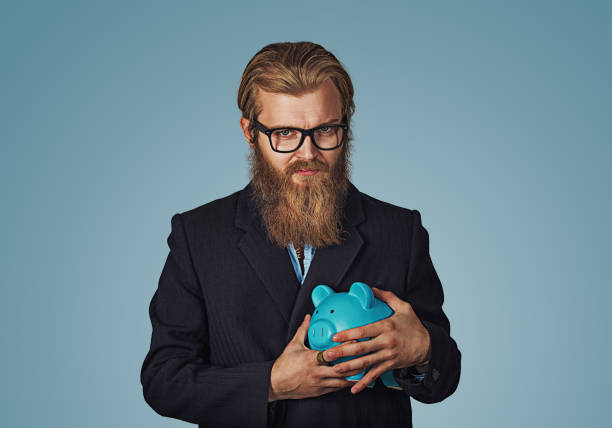 Young greedy stingy business man holding piggy bank Young greedy stingy Bearded hipster businessman man holding piggy bank Isolated on blue studio wall Background. Negative face expression human emotion body language reaction attitude. Horizontal miserly stock pictures, royalty-free photos & images