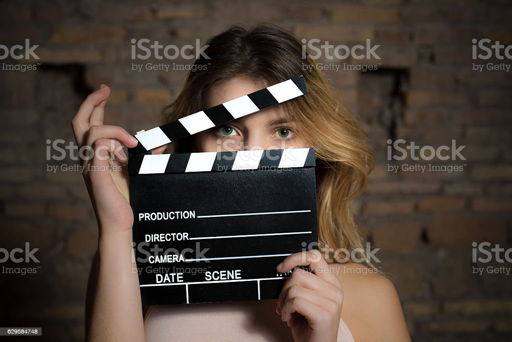 Young green eyes blonde woman with movie clapper stock photo