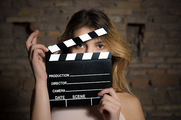 young green eyes blonde woman with movie clapper - audition stock photos and pictures