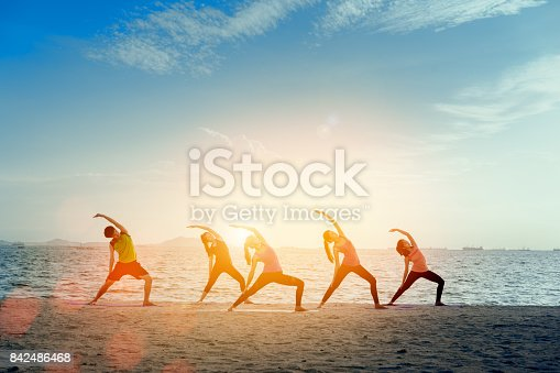 istock Young group man and woman yoga practice on mat relaxation in class exercise with pose fitness sport for healthy on the beach and seaside  modern city at sunrise relax holiday vacation time in summer. 842486468