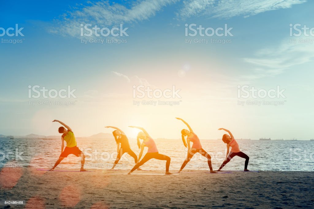 Young group man and woman yoga practice on mat relaxation in class exercise with pose fitness sport for healthy on the beach and seaside  modern city at sunrise relax holiday vacation time in summer. stock photo