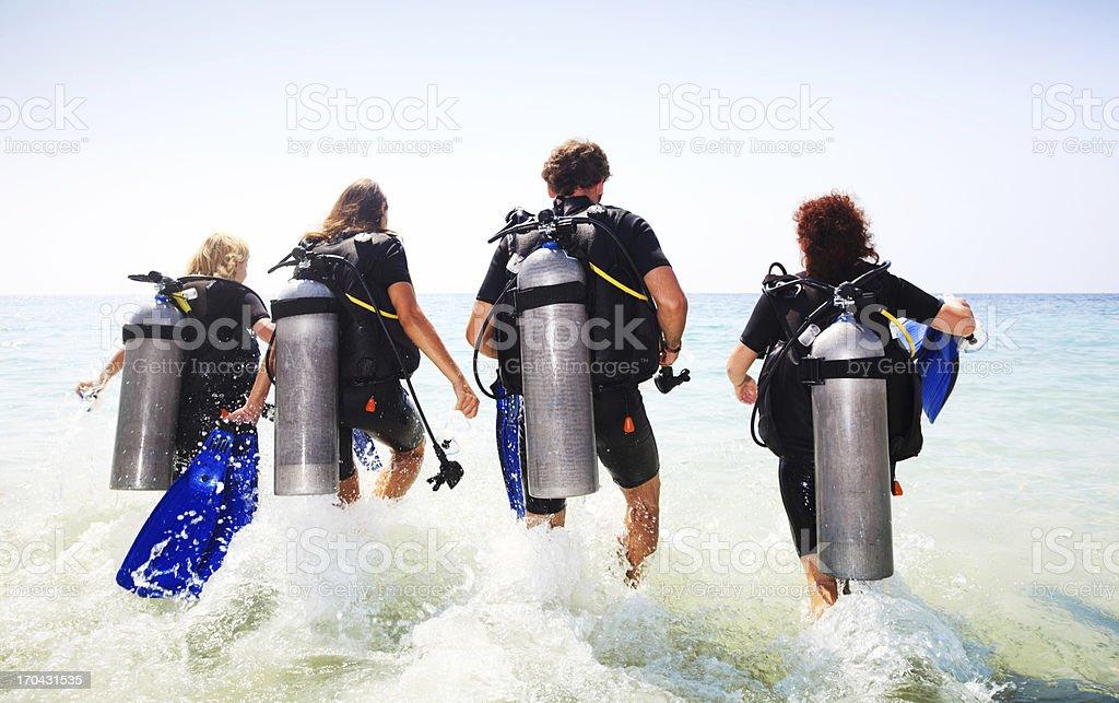 Grupo de jovens mergulhadores entrar na água. - foto de acervo