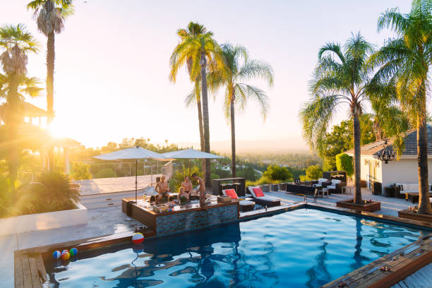 Young group of friends staying in a luxury villa enjoying the hot tub as the sun sets Young group of friends staying in a luxury villa enjoying the hot tub as the sun sets. Los Angeles, America. July 2017 holiday villa stock pictures, royalty-free photos & images