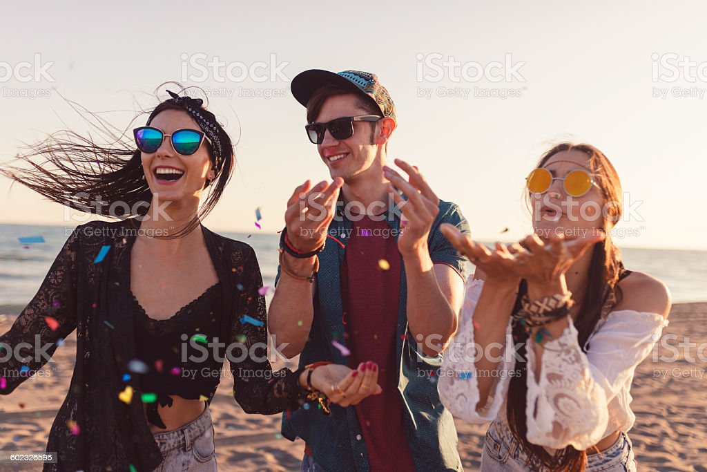 Young group of friends throwing confetti on the beach foto