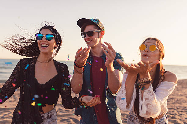 Young group of friends throwing confetti on the beach - foto stock