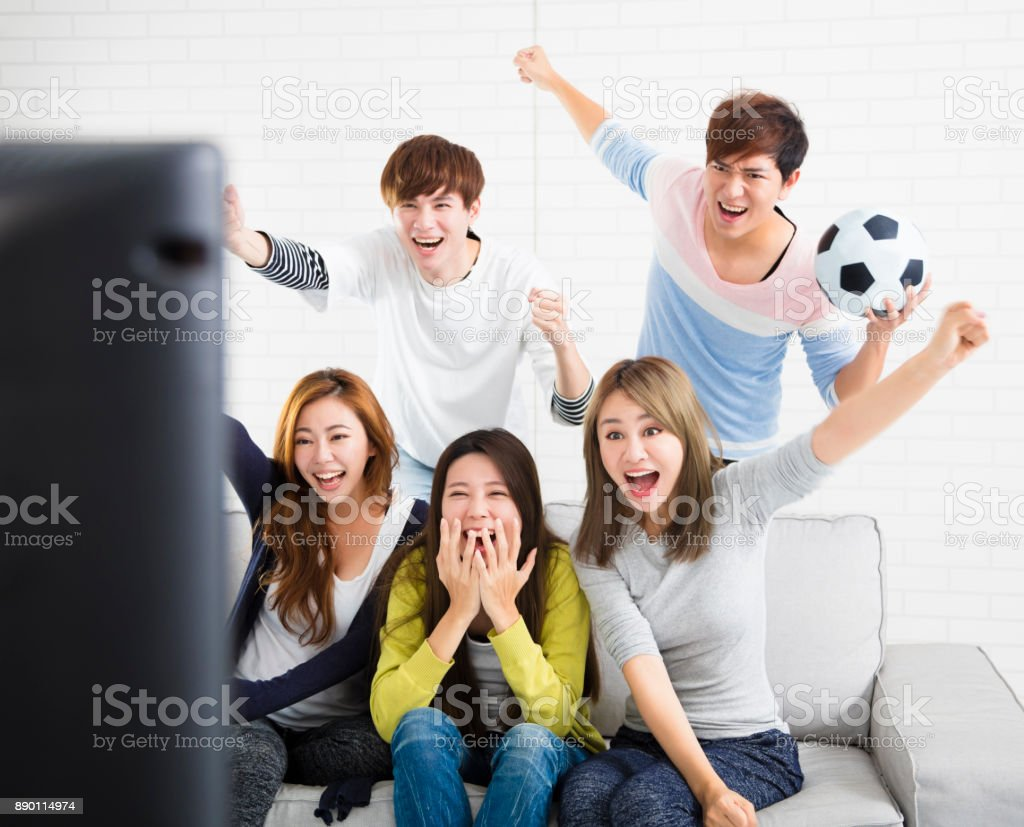young group Watching Sports On Television And Cheering stock photo