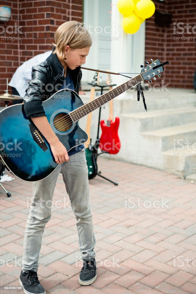Young guitar player rehearsing before show in family driveway. stock photo