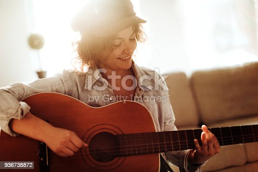 istock Young guitarist practising at home 936738872